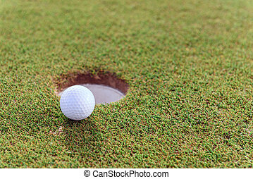 Close up of golf ball near hole - Just little Close up of...