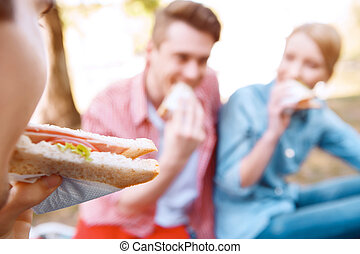 Young people eating sandwiches during picnic - First bite...