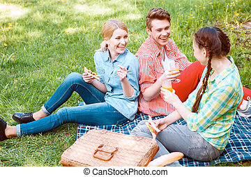 Young people eating and drinking during picnic - With...