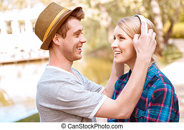 Handsome man putting headphones on pretty girl - Trying on...