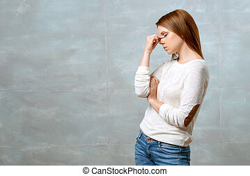 Woman standing and touching bridge of her nose - Feeling...
