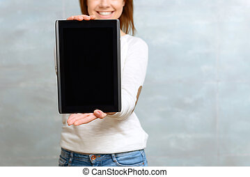 Smiling woman showing her tablet. - Look here. Close up of...
