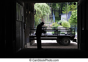 Amish Man Silouetted in his His Barn Door - An image of a...