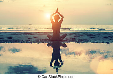 Silhouette of yoga woman at sunset