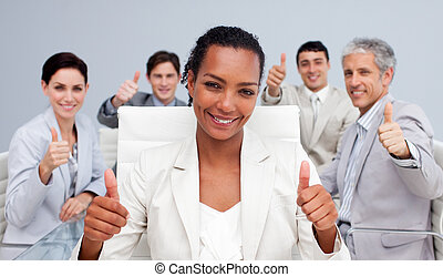 Happy business team celebrating a sucess with thumbs up in...