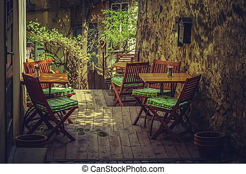 Homey outdoor cafe terrace setting with wooden chairs and...