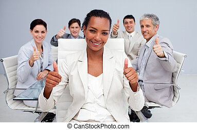 Afro-American businesswoman and her team with thumbs up in...