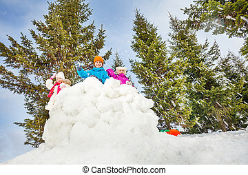 Children playing snowball fight game together standing...
