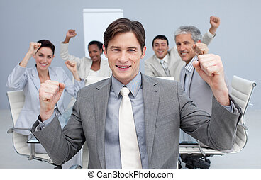 Happy business team celebrating a sucess with hands up in...