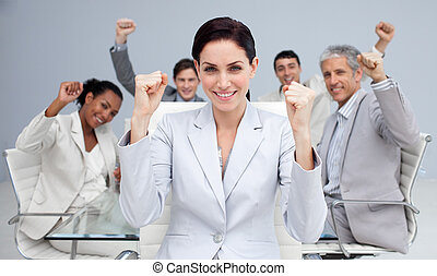 Happy business people celebrating a sucess with hands up in...