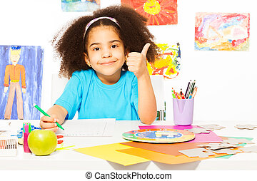 African girl holds thumbs up at the desk writing - African...