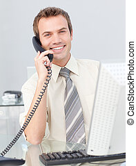 Attractive Businessman talking on phone in the office and working with a co