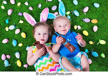 Kids eating chocolate rabbit on Easter egg hunt - Children...