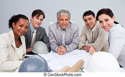 Architects in a meeting studying plans - Smiling architect...