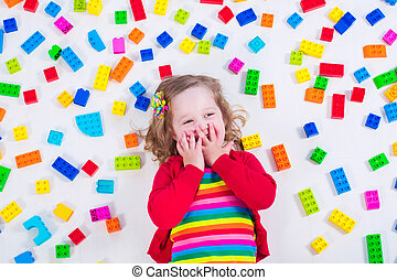 Little girl playing with colorful blocks - Child playing...