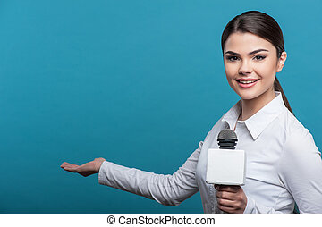 Beautiful girl TV journalist with pretty smile is reporting...