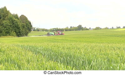 tractor crop sprayer - farmer spraying crop field at summer...