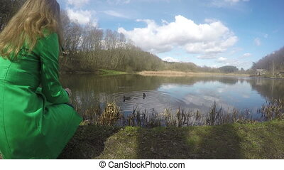 girl feed duck on shore - girl with green raincoat feed the...