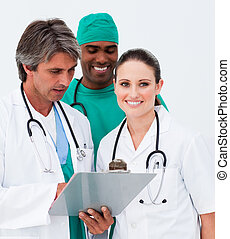 Attractive female doctor taking notes with her colleagues in...