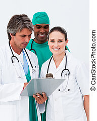 Smiling female doctor taking notes with her colleagues in...