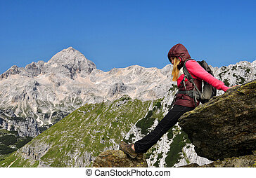 Girl on rock, in the background mount Triglav - Slovenia