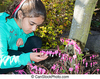 Girl Enjoying Time In Garden Observing Flowers - Young...