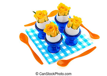 Easter flowers in egg cups with plastic spoons