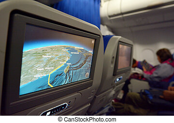 Interior of airplane with a route on a screen map -...
