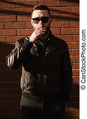 Front view of handsome bearded man smoking a cigarette over...