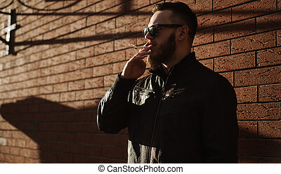 Side view of handsome bearded man smoking a cigarette over...