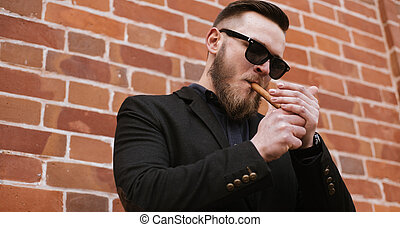Side view of handsome bearded man smoking a cigar