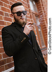Handsome bearded man smoking a cigarette over brick wall