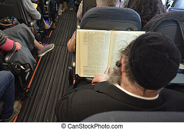 Orthodox Jewish man pray on a airplane during flight -...