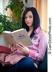 young religious woman reading the holy bible