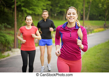 Smiling friends running outdoors. Sport fitness friendship...
