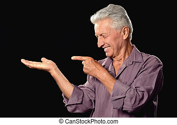 Mature man pointing with his fingers on black background