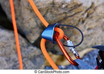 climbing carabiner on orange rope, close up
