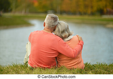 Back view of elderly couple together over natural background