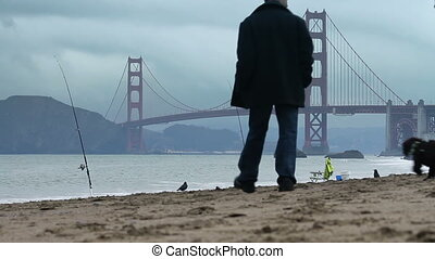 Baker Beach Dog Walk - A couple walks their dog along Baker...