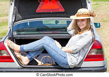 young woman sitting in car trunk outdoor