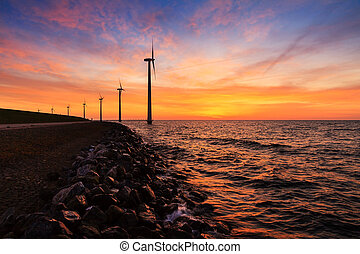 Sunset wind turbines - Beautiful sunset at the dike with...
