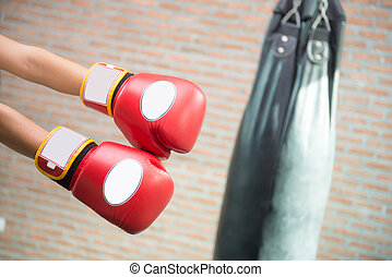 Boxer is punching a sandbag - Boxer in red boxing gloves is...