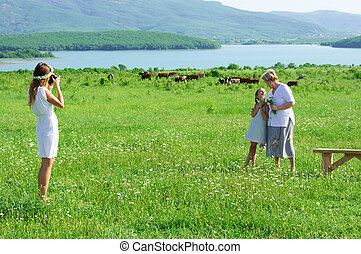 Family taking photos - Young woman taking photos her...