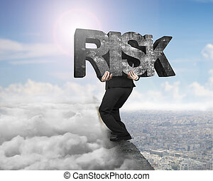 Man carrying risk concrete word on ridge with cloudscape...