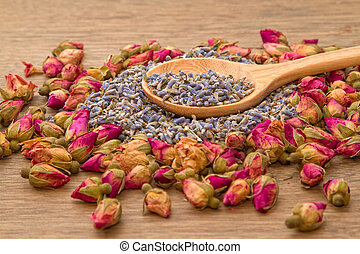 Dried lavender and rose flower tea in wooden spoon