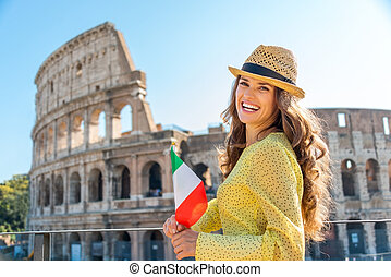 Woman holding flag and smiling at Colosseum in Rome - A...