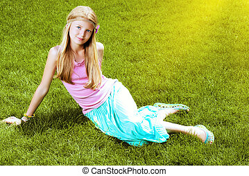 natural girl - Beautiful teenage girl lying on a green lawn...