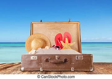 Travel concept with old suitcase on wooden planks full of...
