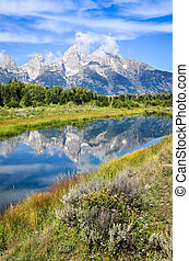 View of Grand Teton mountains with water reflection and...