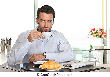 man drinking coffee in cafe with croissant and newspaper on...